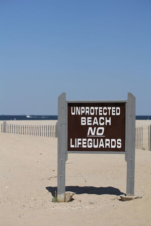 unprotected: A sign reads  Unprotected Beach No Lifeguards   A clear blue sky is seen in the background along with a beach fence and ocean in the distance  Shallow depth of field