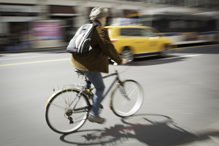 evident: A man bicycles through the city streets of New York  Panning was used to capture photo and blur and movement is evident  Editorial