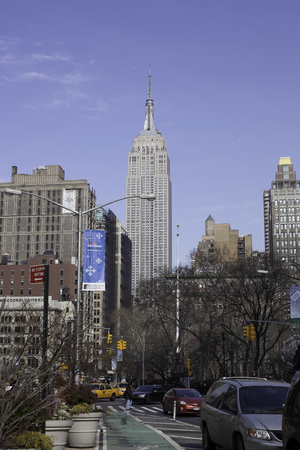 The famous Empire State Building can be seen from Broadway in New York City.  A crisp blue winter sky surrounds the skyline. Madison Square Park is off to the right in the photograph. At close view, you can actually see people on one of the observation de