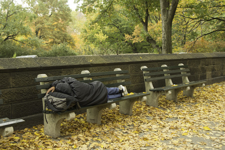 A homeless person sleeps on a park bench outside of Central Park in New York City.