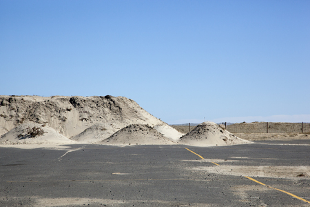 Piles of sand sit in a parking lot adjacent to the Atlantic Ocean In Sea Bright, New Jersey.   Photo taken October 15, 2013, almost one year after Hurricane Sandy hit the eastern coast of the United States.