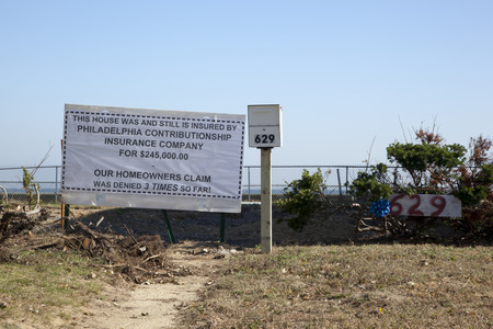 homeowners insurance: A sign stands on property in Union Beach, New Jersey where a home used to sit.  You can see the original walkway.  Photo taken October 15, 2013, almost one year after Hurricane Sandy hit the eastern coast of the United Staes.