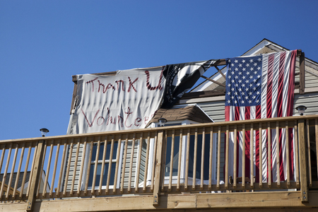 A house has been raised up and put on stilts in the Highlands, New Jersey.  A sign saying Thank you Volunteers hang on the balcony along with a POW flag and an American flag. Photo taken October 15, 2013, almost one year after Hurricane Sandy hit the ea