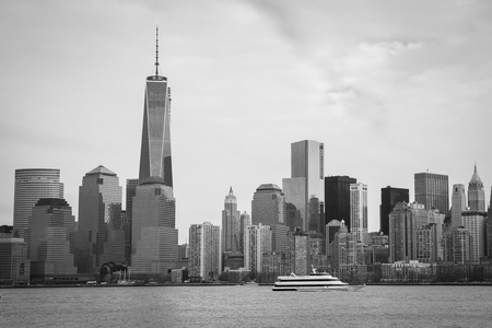 world trade center: A black and white image of the Lower Manhattan Skyline with the World Trade Center Freedom Tower; the Spirit of New Jersey passes in the foreground on the Hudson River