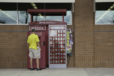 rentals: A man stands in front of a Red Box DVD Rental Machine to get a movie