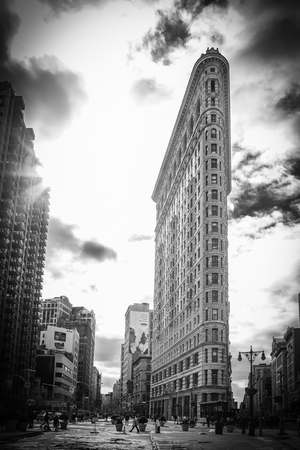 A view of New York City surrounding the famous Flatiron Building where Broadway and Fifth Avenue meet   Beautiful clouds can be seen in the sky and the morning sunlight shines through the tops of the buildings  Madison Square Park is to the left in the ph