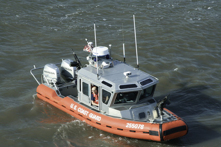 A small U S  Coast Guard boat patrols the Hudson River in New York City     You can see a Coast Guard member looking out of the cabin area of the boat   Automatic weapons are mounted on the front and back of the boat   Photograph taken April 19, 2008