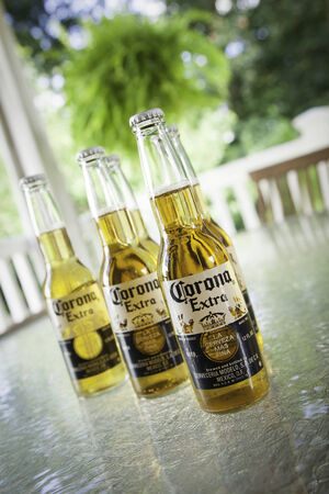 Corona Mexican beers sit on a glass patio table   You can see greenery in the background  Editorial Use Only   Editorial