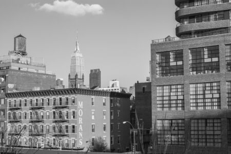 A view from the High Line park in Manhattan, New York City; the Empire State Building can be seen in the background; black and white image; horizontal format