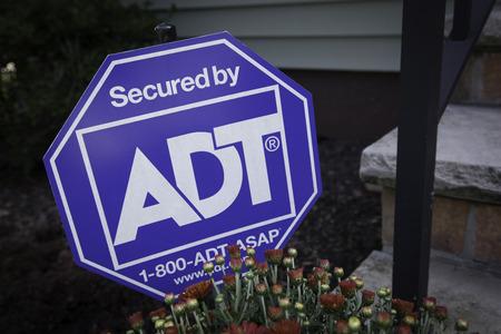 주거용 주택 외부에 ADT 보안 사인이 앉아 있습니다. 구내에있는 가정용 경보 시스템의 침입자를 경고합니다.