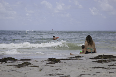 A woman and small child sit in the sand on Honeymoon Island Beach in Dunedin, Florida   They sit and look out at the Gulf of Mexico   Another woman can be seen playing in the surf in front of them   Honeymoon Island has been voted one of the best beaches