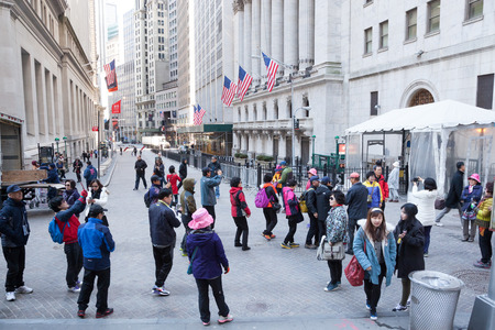 Tourists sightsee and take photos on Wall Street in New York City