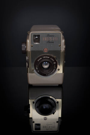 A vintage Kodak Bulls-eye Gold Version with Twindar Lens sits atop a black reflective surface   This camera was in production from 1957-1960, took 620 film, and retailed for  15 US dollars