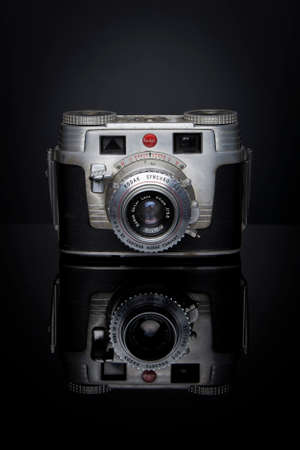 kodak: A Kodak Signet camera with an Ektar Lens sits on a black reflective surface; this camera was marketed from 1951-1958, took 135 film, and retailed for  95 US dollars