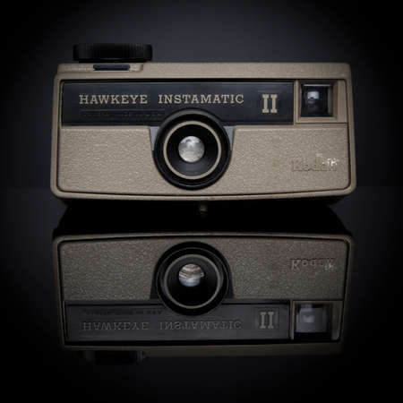 kodak: A Kodak Hawkeye Instamatic II camera sits on a reflective black surface; This camera was marketed from 1969 - 1975 and took 126 film; it was manufactured for promotional use and not for sale in stores