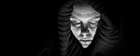 harsh: An ugly, scary looking woman in a black shroud; her eyes are closed as if in despair; very shadowy harsh image; black and white panoramic format