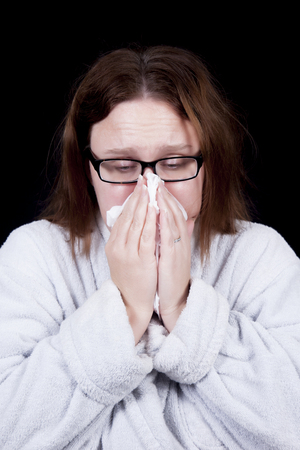 A woman with messy hair blows her nose as she suffers from a cold or the flu   She wears glasses and a bathrobe