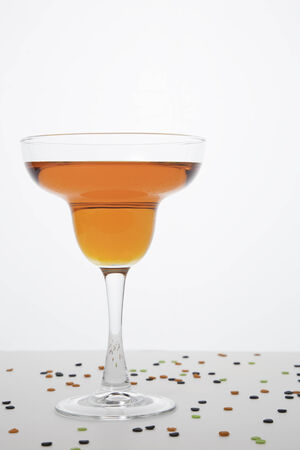 responsibly: An orange colored margarita in a margarita glass on a white background   Confetti type sprinkles in Halloween colors are sprinkled around the glass
