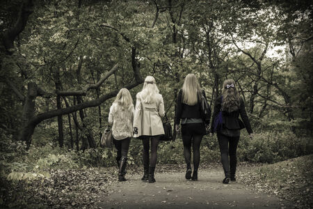 wooded path: A group of four girls walk down a path through a wooded area of a park during the autumn  Stock Photo