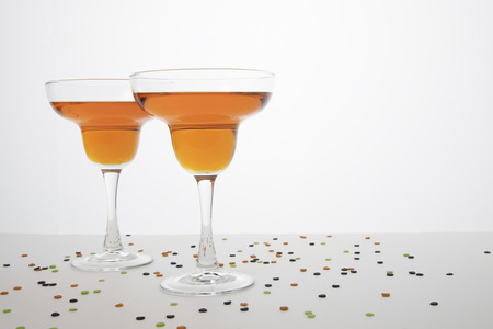 drink responsibly: Two orange colored margaritas in margarita glasses on a white background   Confetti type sprinkles in Halloween colors are sprinkled around the glass