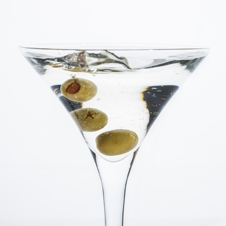 A martini glass on a white background; the water ripples and splashed as a green spanish olive with pimento is dropped into the glass; square format Imagens