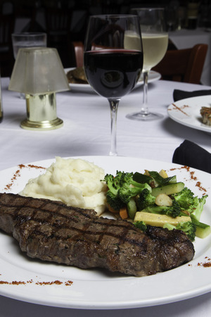 A white plate holds a delicious grilled New York Strip Steak with a side of mashed potatoes and fresh mixed vegetables   A glass of red wine completes the meal   Other dishes and glasses can be seen in the background   Everything is atop a white tableclot