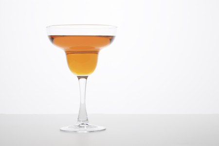 An orange colored margarita in a margarita glass - white background photo