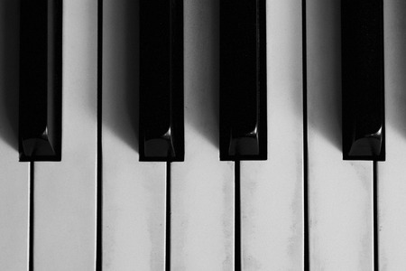 ivories: A closeup of the keys on an old piano; black and white colortone; film grain appearance