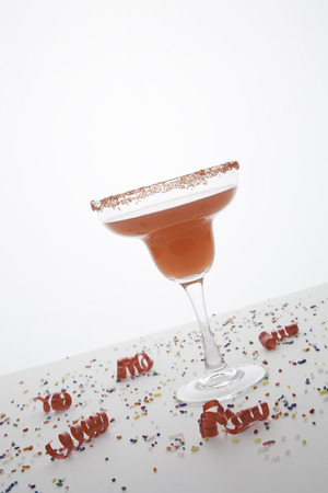 responsibly: A red margarita in a margarita glass is topped with red sugar   Colorful sprinkles and curly red ribbons are sprinkled around the glass   Everything isolated on white  Stock Photo