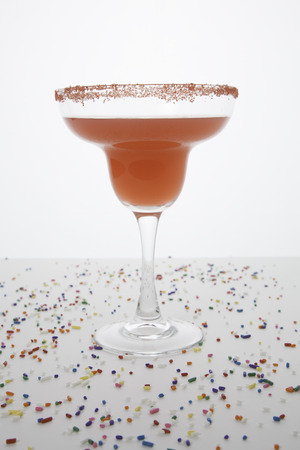 A red margarita in a margarita glass is topped with red sugar   Colorful sprinkles are sprinkled around the glass   Everything isolated on white  photo