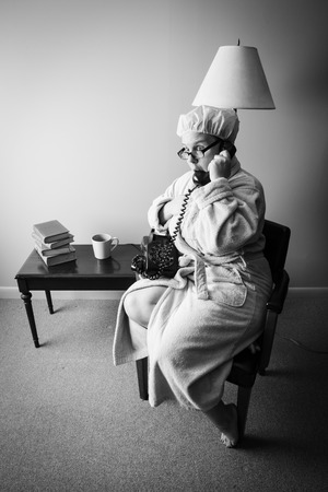 furnishings: Retro mom answers the phone only to get shocking news   She is dressed in a bathroom and shower cap; Classic rotary phone, mid-century modern furnishings; black and white colortone Stock Photo