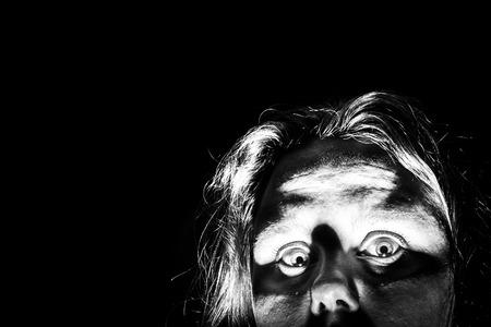 monster movie: A woman peeks out from the corner of a picture as if she is checking to see if it is safe to come out   Looks like a horror movie; black and white colortone Stock Photo