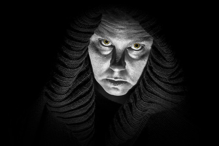 A scary, ugly lady wears a black shroud; glowing monster eyes; black and white image