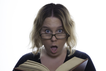 A woman is reading an old book and looks surprised or shocked at something she has just read   She is wearing reading glasses   Pure white background  photo