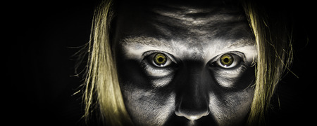 A panoramic photo of a zombie with bright yellow zombie eyes