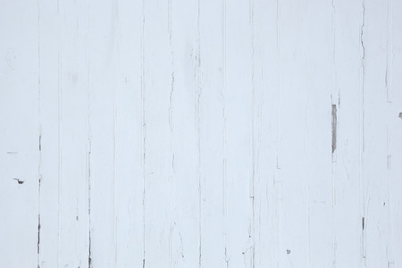 Old white painted wood siding with peeling paing.
