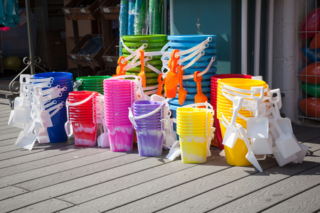 Stacks of brightly colored beach pails sit outside a boardwalk shop for sale. photo
