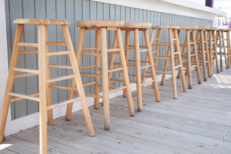 tiki bar: Simple wooden bar stools are lined up at an outdoor bar.