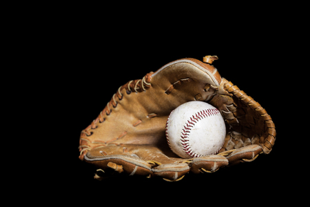 lit image: A worn baseball sits inside an old baseball glove on a solid black background.  Image was lit by using a lightpainting technique. Stock Photo