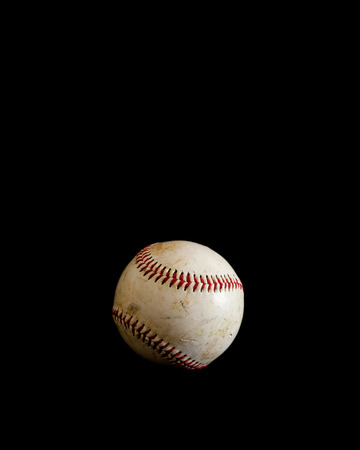 black leather: A worn baseball sits alone on a solid black background.