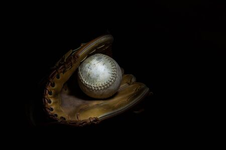 A worn softball sits inside an old baseball glove on a solid black background. Image was lit by using a lightpainting technique.