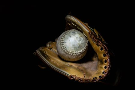 softball: A worn softball sits inside an old baseball glove on a solid black background.  Image was lit by using a lightpainting technique.