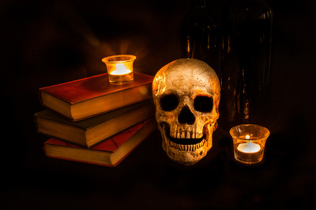 A vintage skull sits beside a stack of old novels and wine bottles; image created with a light painting technique photo