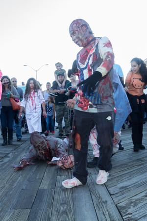 wander: ASBURY PARK, NJ - October 3, 2014:  Zombies wander the Asbury Park Boardwalk during the 2014 New Jersey Zombie Walk. Editorial