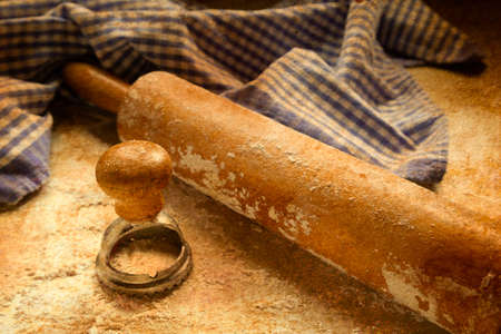preperation: An antique rolling pin sits on a floured surface a ravioli press and a checkered blue and white towel.