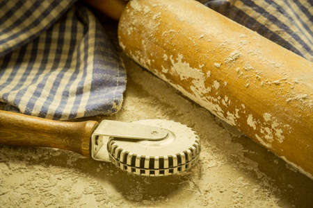 crimper: An antique rolling pin sits on a floured surface a pie crust crimper and a checkered blue and white towel.