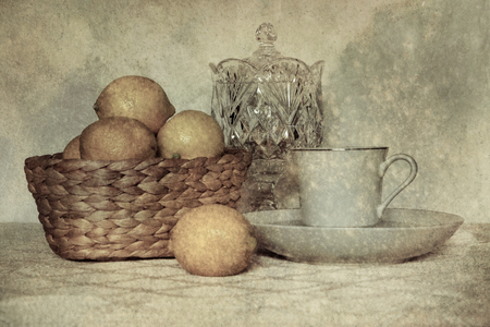 crystal bowl: A teacup sits on a pretty tablecloth with a crystal bowl and a basket of fresh lemons.