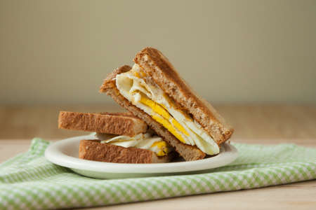 checker plate: A fried egg sandwich on whole grain toast sits on a white plate atop a green and white checked napkin and a wooden cutting board.