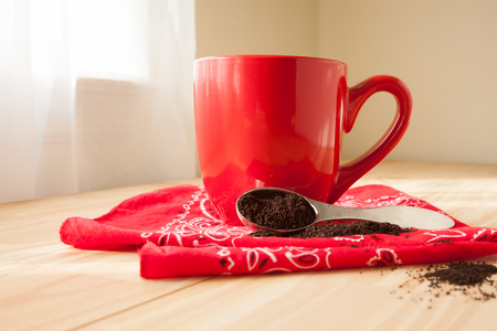 A red coffee mug sits atop a red bandana napkin.  A scoop of coffee grounds is spilled around and sits beside the mug.