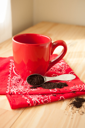 red bandana: A red coffee mug sits atop a red bandana napkin.  A scoop of coffee grounds is spilled around and sits beside the mug.